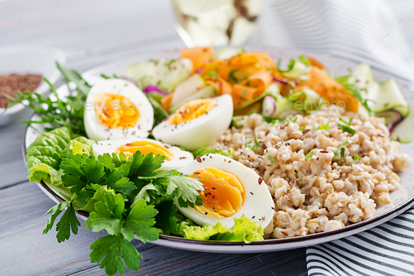 Breakfast bowl with oatmeal, zucchini, lettuce, carrot and boiled egg. Fresh salad. Healthy food - Stock Photo - Images
