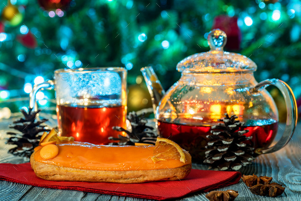 Cozy still life with tea, candle light and eclairs - Stock Photo - Images