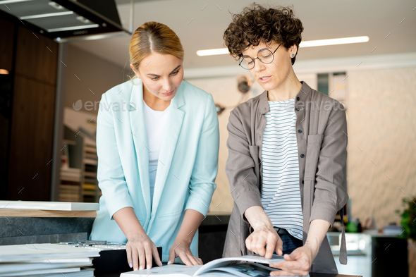 Young creative designer pointing at page of catalogue while helping client - Stock Photo - Images