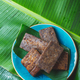 Easter Island Tahitian Polynesian banana pie pupping POE on blue plate on banana palm tree leaves. - PhotoDune Item for Sale