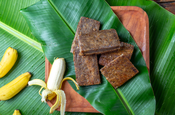 Easter Island Tahitian Polynesian banana pie pupping POE on wooden plate on banana palm tree leaves. - Stock Photo - Images