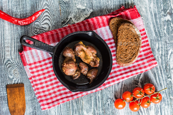 Top view roasted chicken giblets in pan and bread - Stock Photo - Images