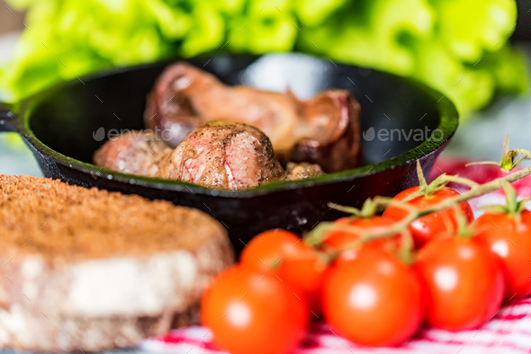 Tasty roasted chicken giblets in pan and rye bread - Stock Photo - Images