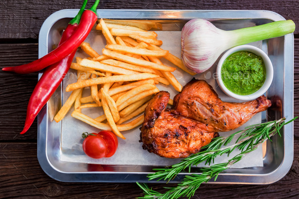Top view meal with chicken thigh, french fries, chili pepper and garlic - Stock Photo - Images