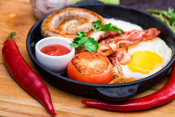 Nutritious meal with fried egg, sausage, bacon, tomato and sauce in frying pan - Stock Photo - Images