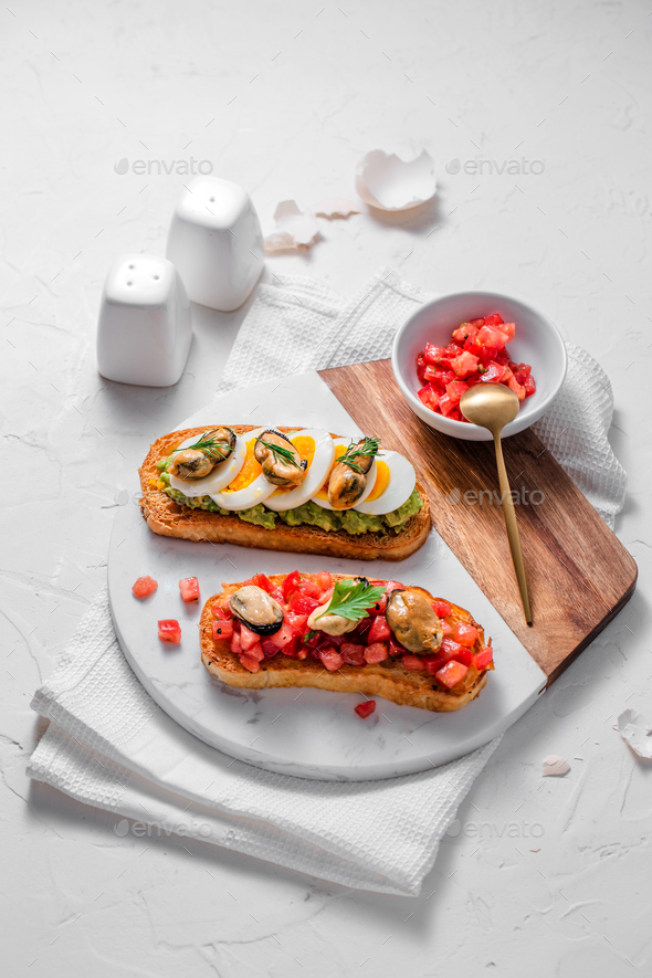 Toasted bread with tomatoes and smoked mussels - Stock Photo - Images