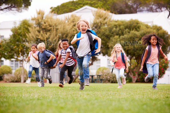 Excited Elementary School Pupils Running Across Field At Break Time - Stock Photo - Images