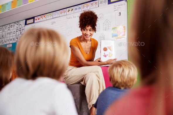 Female Teacher Reading Story To Group Of Elementary Pupils In School Classroom - Stock Photo - Images