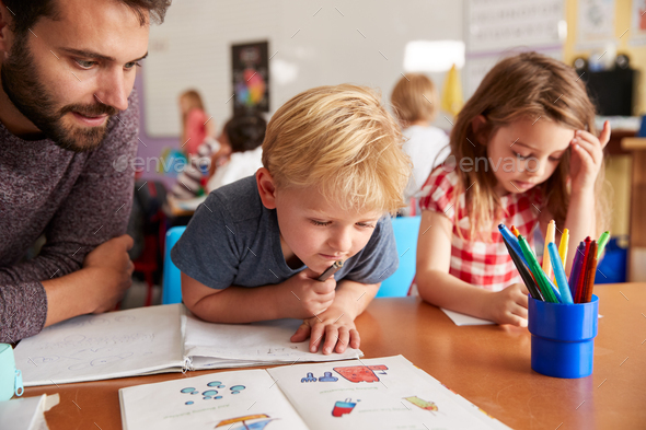 Elementary School Teacher Helping Pupils As They Work At Desk In Classroom - Stock Photo - Images