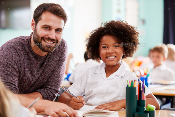 Portrait Of Male Elementary School Teacher Giving Female Pupil Wearing Uniform One To One Support - Stock Photo - Images