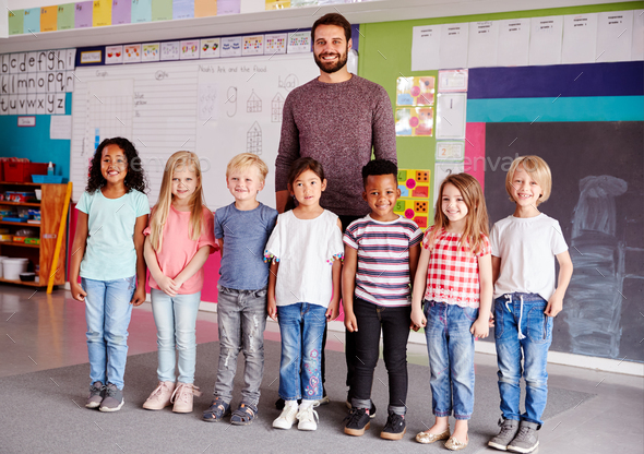 Portrait Of Elementary School Pupils Standing In Classroom With Male Teacher - Stock Photo - Images