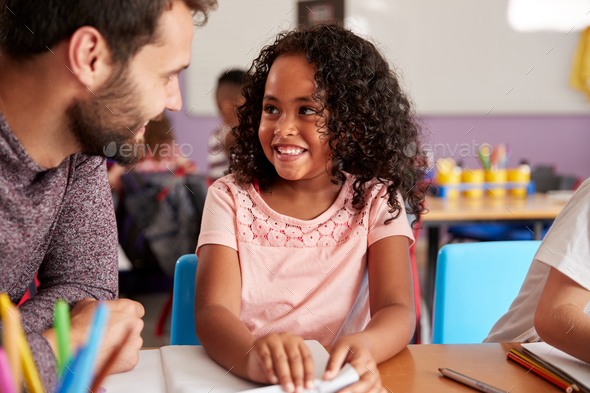 Elementary School Teacher Giving Female Pupil One To One Support In Classroom - Stock Photo - Images