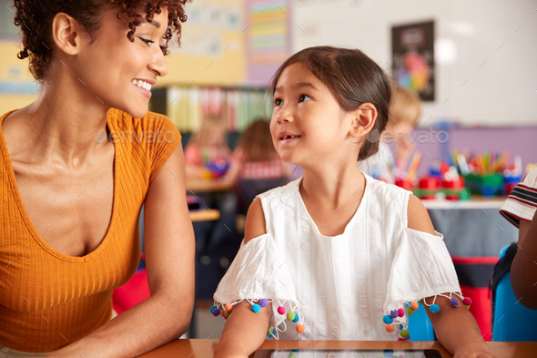 Elementary School Teacher And Female Pupil Drawing Using Digital Tablet In Classroom - Stock Photo - Images