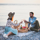 Young happy couple having picnic with sparkling wine at seaside - PhotoDune Item for Sale