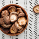 Chinese dried mushrooms Shiitake in a wooden bowl on a table - PhotoDune Item for Sale