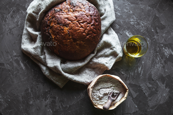 Bread on a black background with flour and oil. The bread is on the towel. homemade food - Stock Photo - Images