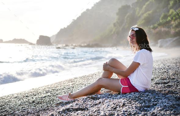 Young woman smiling at pebble beach at Mediterranean sea - Stock Photo - Images