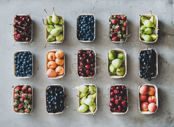 Flat-lay of fresh fruits and berries over grey concrete background - Stock Photo - Images