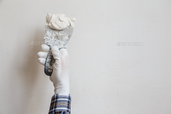 Worker in white gloves performs plastering of the walls of the room - Stock Photo - Images