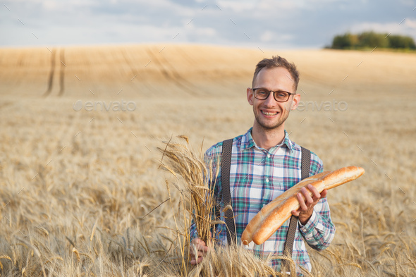 Happy farmer hold bakery products and ears of corn standing in ripe wheat field - Stock Photo - Images