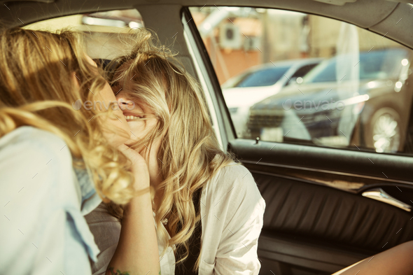Young lesbian's couple preparing for vacation trip on the car in sunny day - Stock Photo - Images
