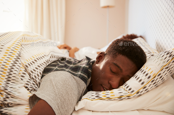 Young African American man lying asleep in bed in the morning - Stock Photo - Images