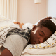 Young African American man lying asleep in bed in the morning - PhotoDune Item for Sale