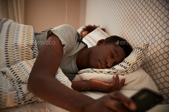 Millennial African American man half asleep in bed holding smartphone - Stock Photo - Images