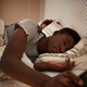 Millennial African American man half asleep in bed holding smartphone - PhotoDune Item for Sale