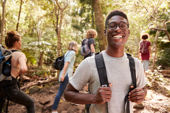 Waist up portrait of smiling millennial African American man hiking in a forest with friends - Stock Photo - Images