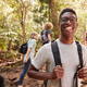 Waist up portrait of smiling millennial African American man hiking in a forest with friends - PhotoDune Item for Sale