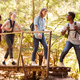 Young African American man turning to friends as they cross a footbridge during a hike in a forest - PhotoDune Item for Sale