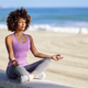 Black woman, afro hairstyle, in lotus asana with eyes closed in the beach - PhotoDune Item for Sale