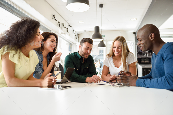 Multi-ethnic group of young people studying together on white desk - Stock Photo - Images