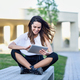 Middle-age woman using digital tablet sitting outdoors in urban background - PhotoDune Item for Sale