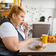 Fat woman eating doughnuts in fastfood restaurant - PhotoDune Item for Sale
