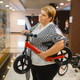 Fatty woman holding little bicycle in mall - PhotoDune Item for Sale