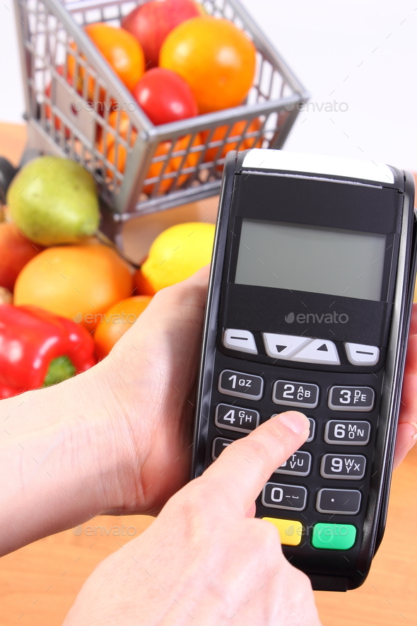 Using payment terminal, fruits and vegetables, cashless paying for shopping concept - Stock Photo - Images