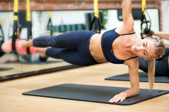 Woman doing suspended elbow side plank with trx - Stock Photo - Images