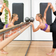 Woman doing dance pose while holding barre at gym - PhotoDune Item for Sale