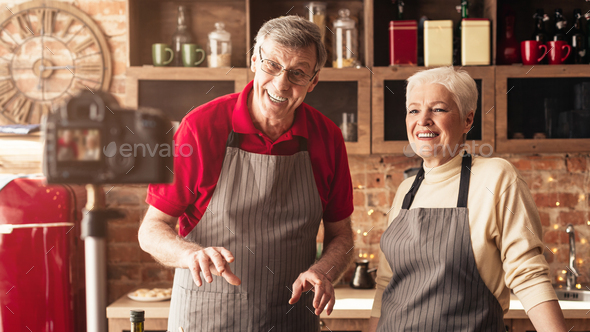 Modern senior couple recording video for their food blog at kitchen - Stock Photo - Images