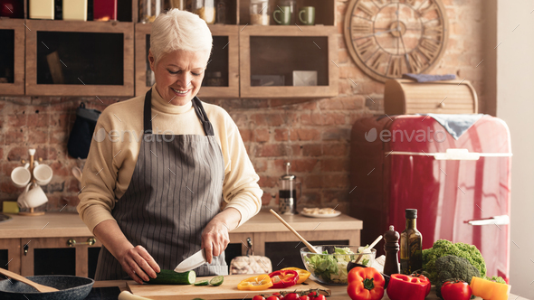 Caring grandmother preparing healthy lunch for family at kitchen - Stock Photo - Images