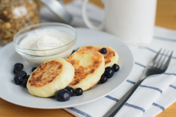 fried circular syrniki, tvorozhniki or cheese cake with sour cream and hot drink - Stock Photo - Images