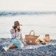 Young woman having picnic at sunset at seaside with appetizers - PhotoDune Item for Sale
