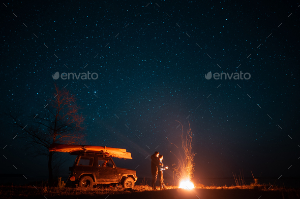 Happy couple man and woman standing in front burning bonfire - Stock Photo - Images