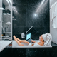 Relaxed woman with towel on hair lying in bathtub - PhotoDune Item for Sale
