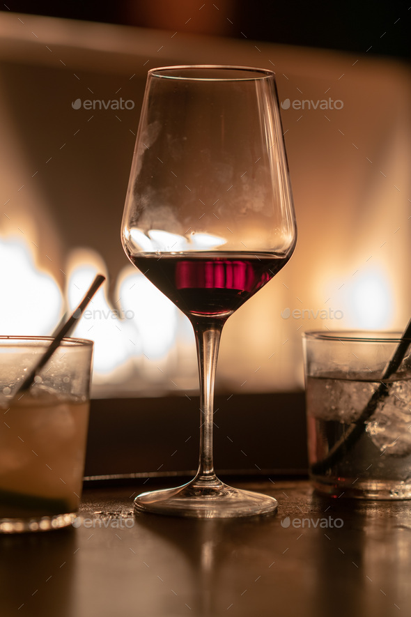 Close up of glasses of vodka, rum and red whine against fire pit - Stock Photo - Images