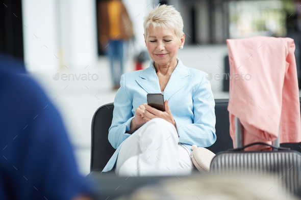 Blond woman using gadget in airport - Stock Photo - Images