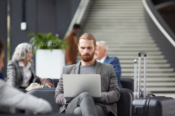 Concentrated guy working in airport - Stock Photo - Images