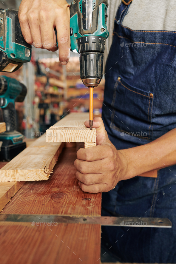 Carpenter using long drill bit at work - Stock Photo - Images